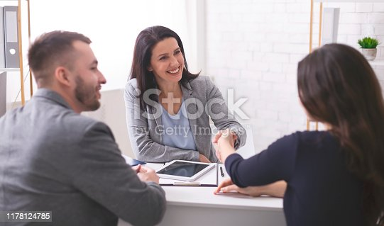 1008974324 istock photo Positive insurance broker handshaking with young couple 1178124785