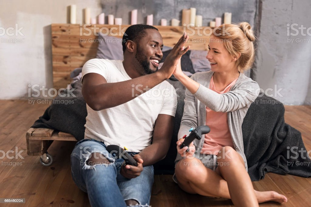 Positive international couple relaxing at home stock photo