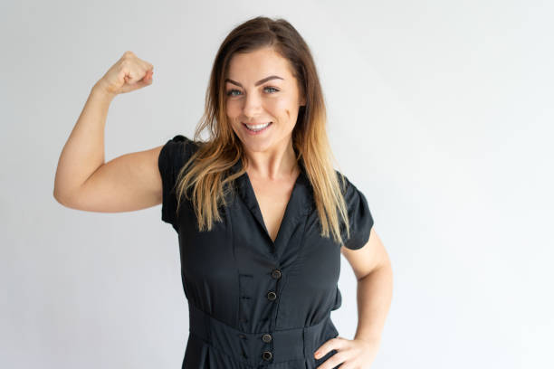 Positive joyful lady showing hand muscles Positive joyful lady showing hand muscles. Middle aged Caucasian woman in casual wear flexing bicep. Strength or feminism concept flexing muscles stock pictures, royalty-free photos & images