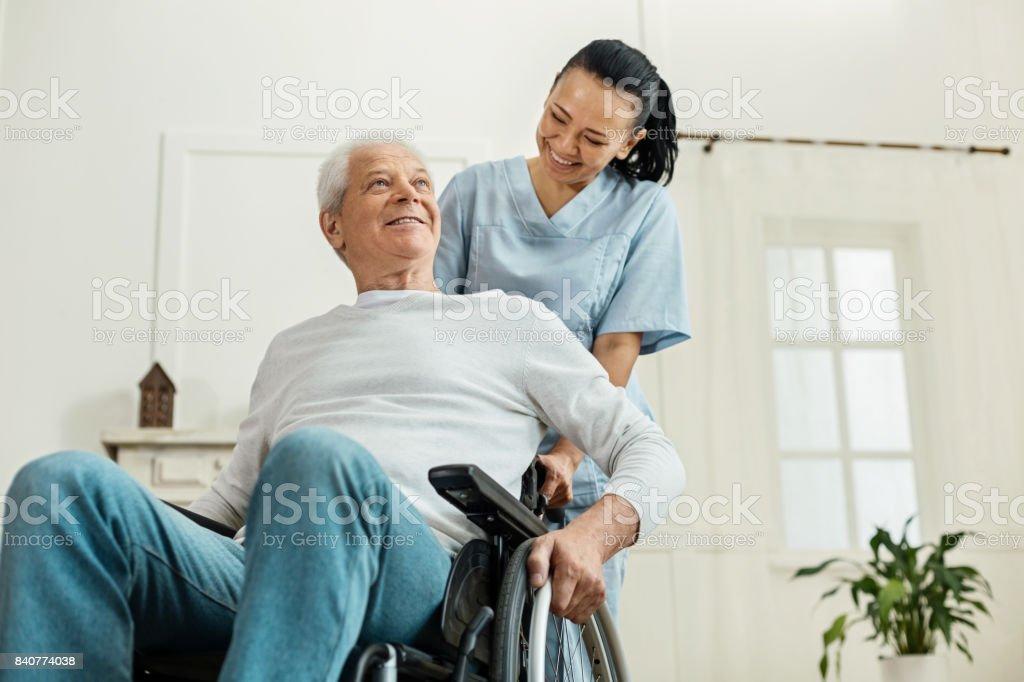 Positivo alegre homem sentado na cadeira de rodas - foto de acervo