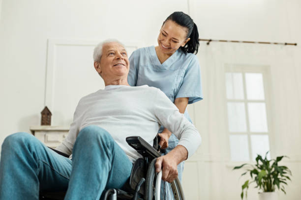 Positive joyful man sitting in the wheelchair Partial paralysis. Positive joyful aged man sitting in the wheelchair and smiling while being helped by a nice professional caregiver paralysis stock pictures, royalty-free photos & images