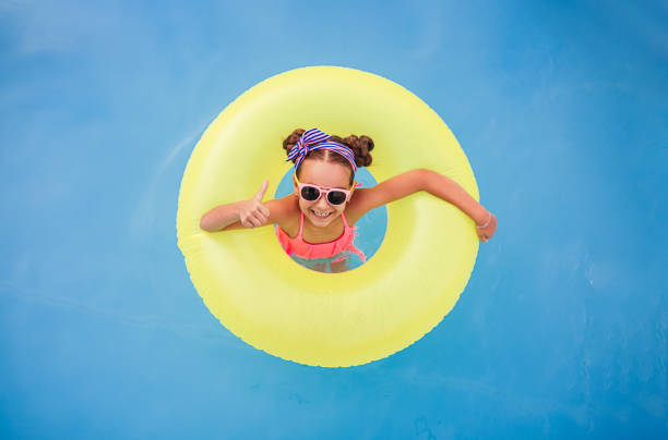 Positive kid with float gesturing thumb up in pool stock photo
