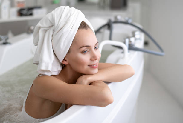 Positive lady leaning on bath stock photo