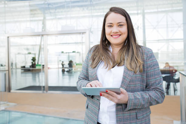 Positive Dame mit Tablet posiert im Business Center – Foto