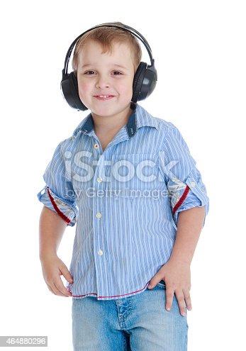 istock Positive little boy in big black headphones 464880296