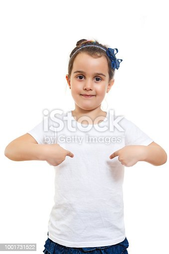 Positive little girl in casual white t shirt indicates at blank space for logo design