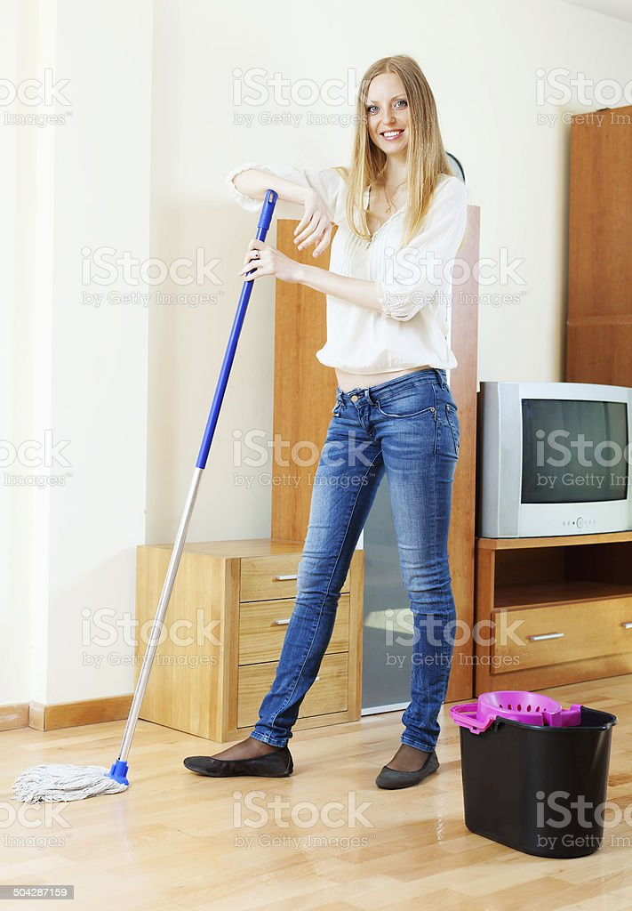 Positive long-haired girl washing parquet stock photo