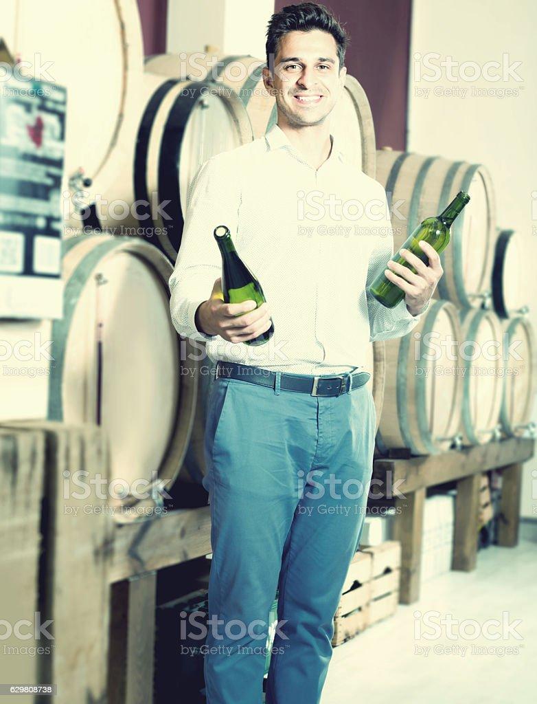 Positive male customer having bottles of wine in shop stock photo