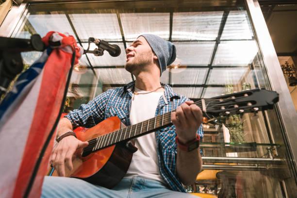 Positivo masculino guitarrista cantando con la guitarra en la barra - foto de stock