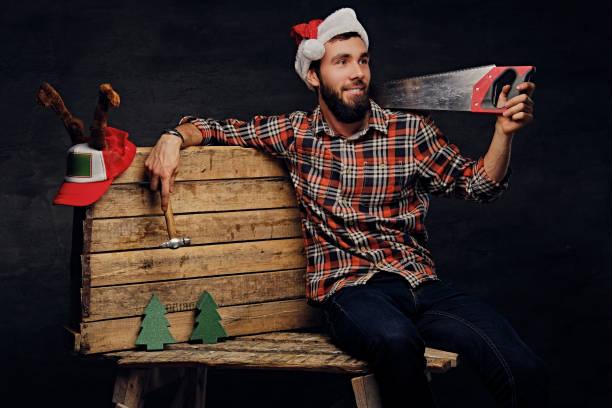 positiven mann sitzt auf holzpalette und handsäge hält. - waldhandwerk stock-fotos und bilder