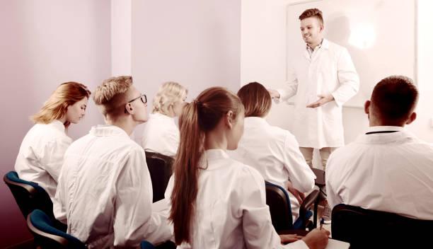 positiven männlichen studenten, die in der nähe von whiteboard zu beantworten - lautsprecher test stock-fotos und bilder