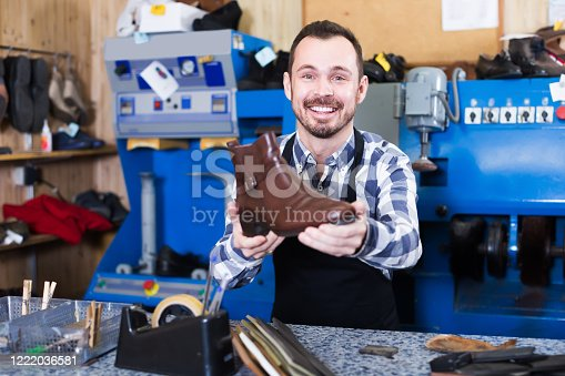 Positive male worker showing fixed shoes in shoe repair workshop