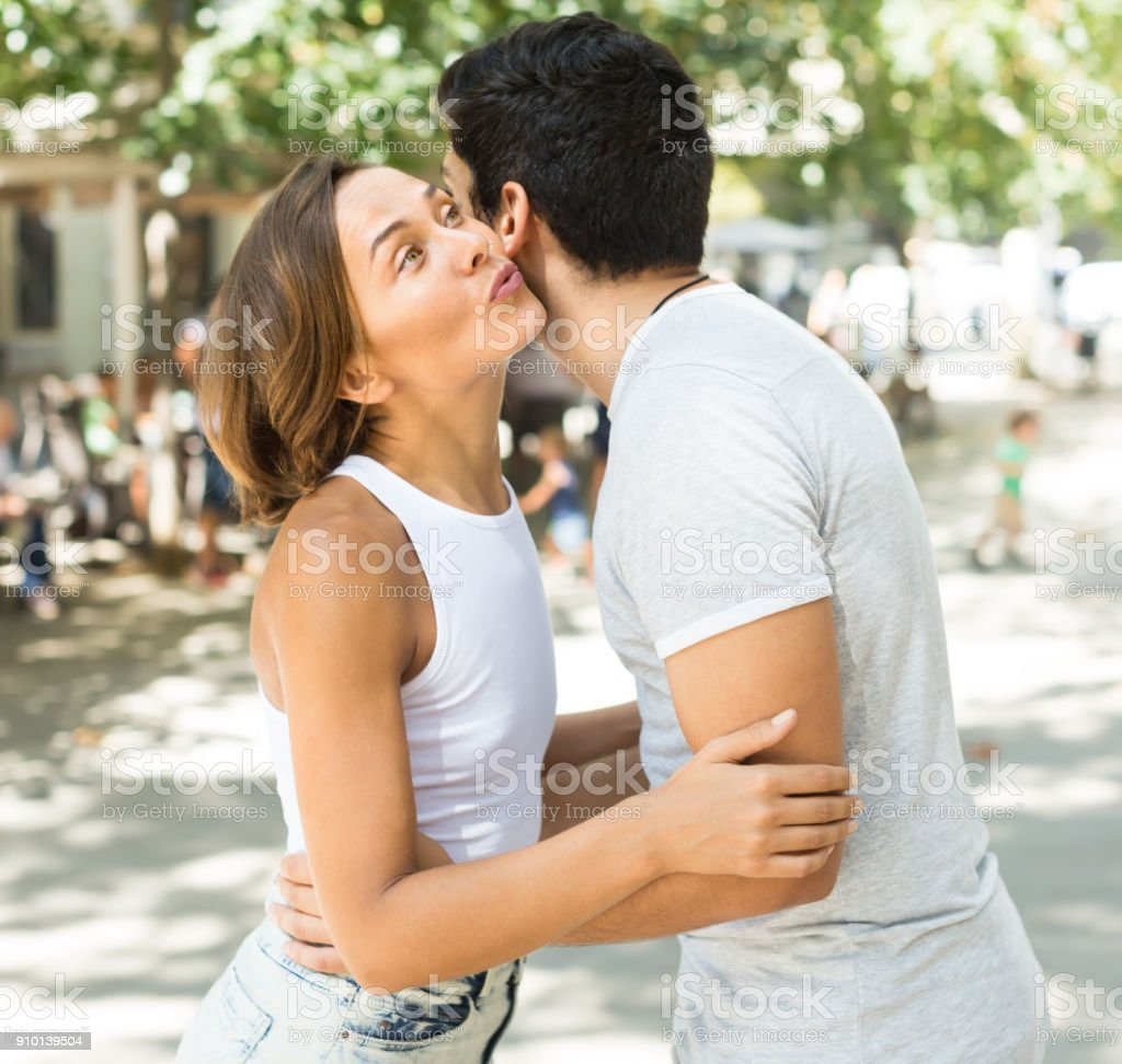 positive man and woman meeting and kissing on the street stock photo