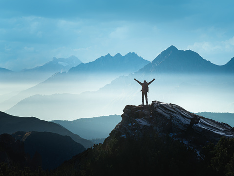 Positive Man standing on top of the mountain with arms raised celebrating his success