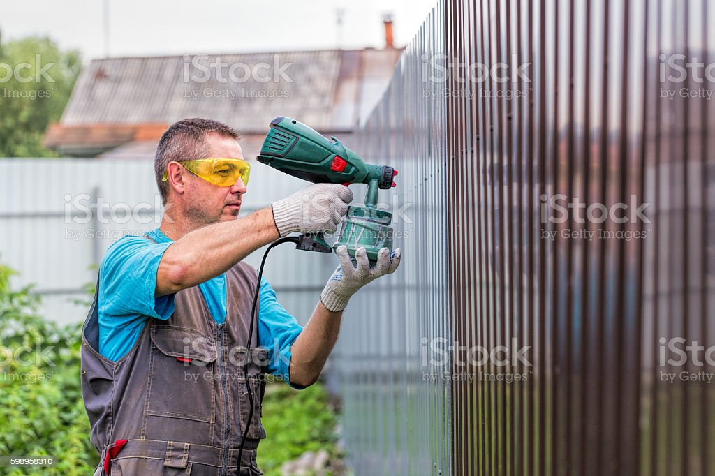 Positive man in overalls with spray gun in hand stock photo