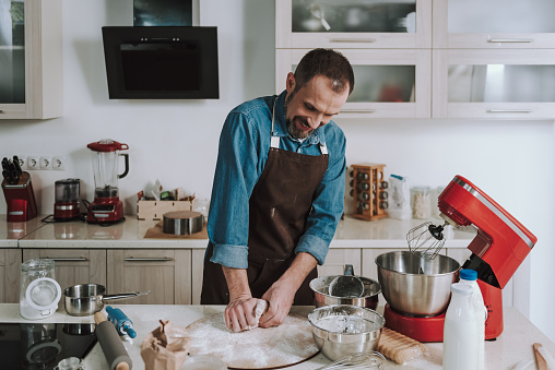Positive man kneading dough and smiling cheerfully