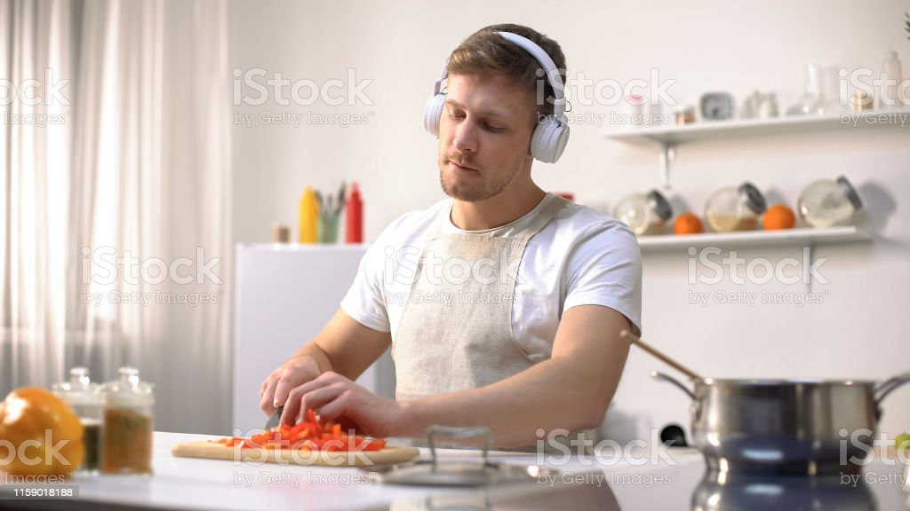 Positive man listening music and cooking vegetables, healthy...