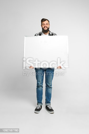 1048561956 istock photo Positive man with mockup poster 1092187760