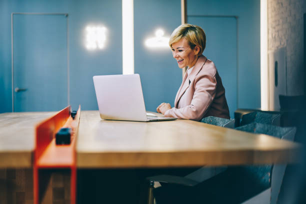 Positive mature coach laughing during watching business webinar online on modern laptop connected to wireless 4G internet.Cheerful female entrepreneur 50 years old reading funny news on netbook stock photo