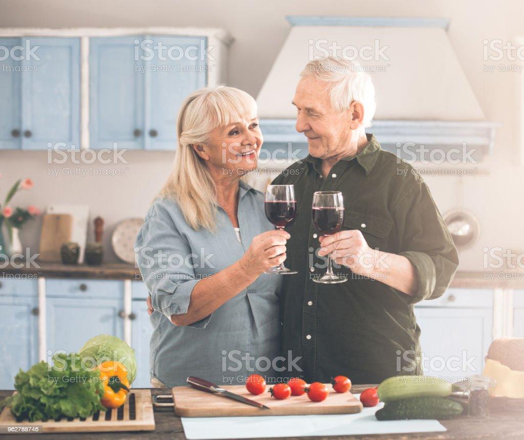 Positive mature loving couple celebrating special event in cook - Foto stock royalty-free di Abbracciare una persona
