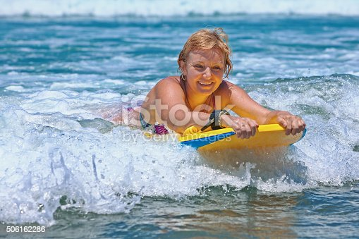 583830686istockphoto Positive mature woman surfing with fun on ocean waves 506162286
