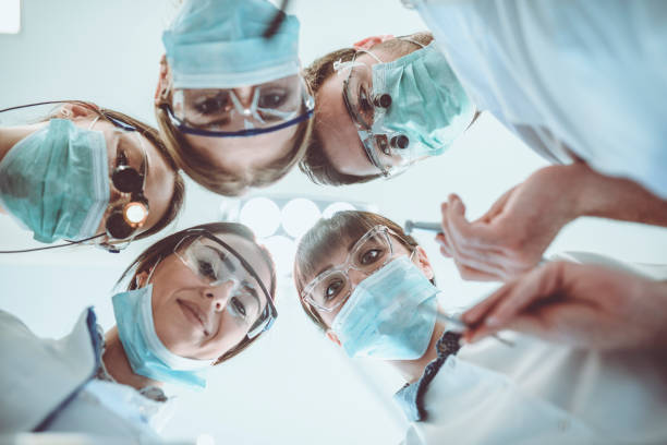 positive medical team waking up the patient from successful surgery - dental assistant stock photos and pictures