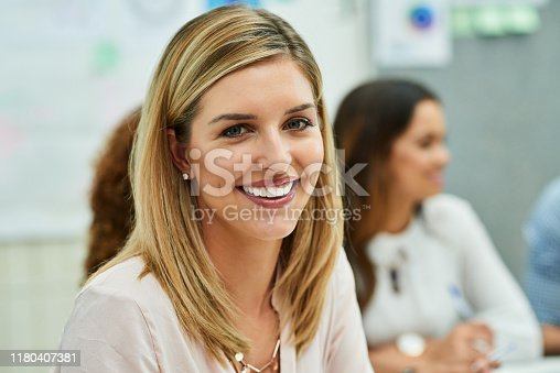 Portrait of an attractive young designer smiling and feeling cheerful during a meeting with colleagues at work