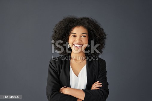 Studio portrait of an attractive young corporate businesswoman posing with her arms folded against a grey background