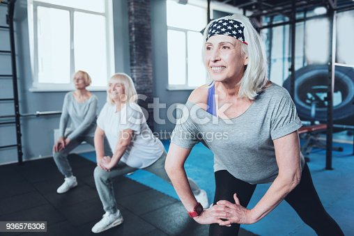 936573360 istock photo Positive minded elderly ladies doing warmup at fitness club 936576306