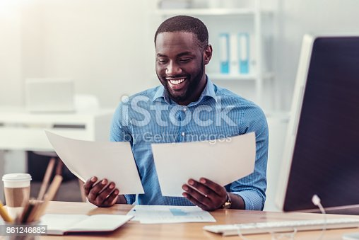 istock Positive minded entrepreneur looking through documents at work 861246682