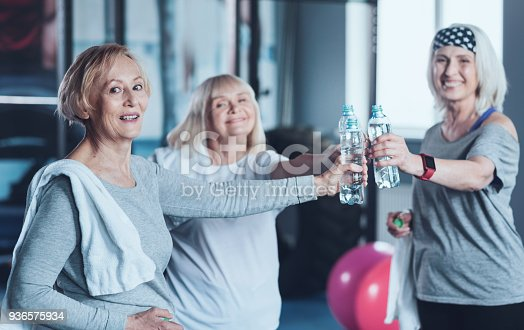 936573360istockphoto Positive minded retired friends joining bottle of water after training 936575934