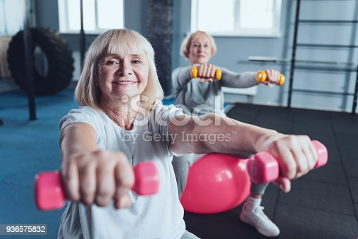 936573360 istock photo Positive minded senior lady enjoying workout at fitness club 936575832