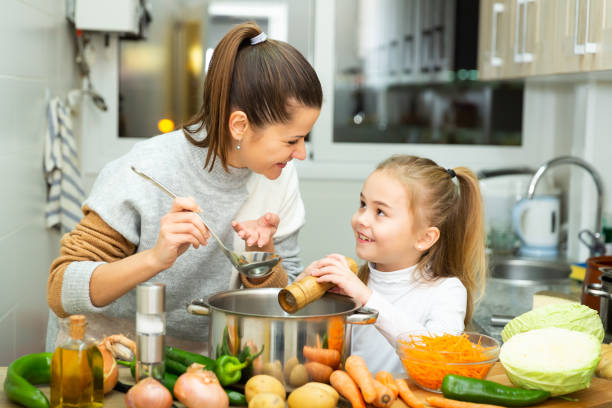 Positive mother and little daughter tasting soup together stock photo