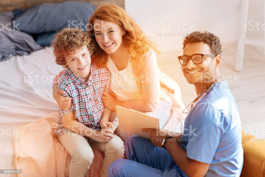 Positive mother embracing her little son stock photo