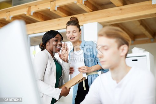 Multi-ethnic employees gossiping about colleague
