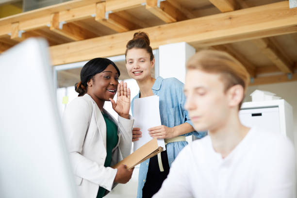 Positive multi-ethnic employees gossiping about male colleague using computer in office, black woman sharing information about newcomer with friend Multi-ethnic employees gossiping about colleague harassment stock pictures, royalty-free photos & images
