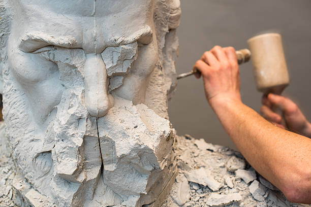 Positive Negative Form. Hands of sculptor and hammer detail while carving. sculpture stock pictures, royalty-free photos & images