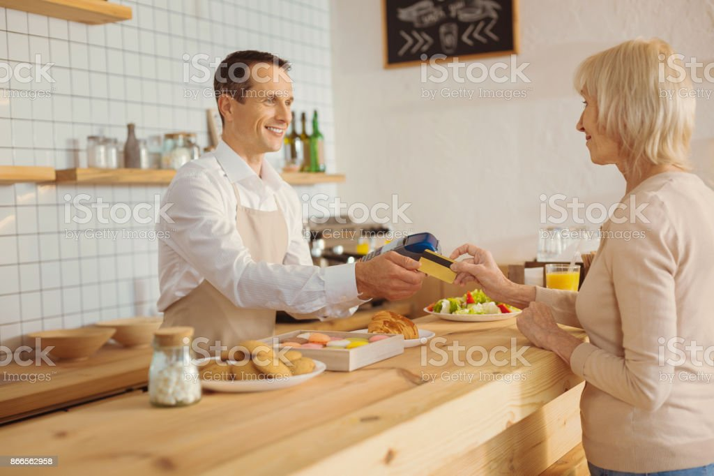 positive nice friendly msn standing at the counter and taking a credit card royalty free