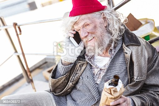 Mobile connection. Positive nice man making a phone call while holding a bottle of beer