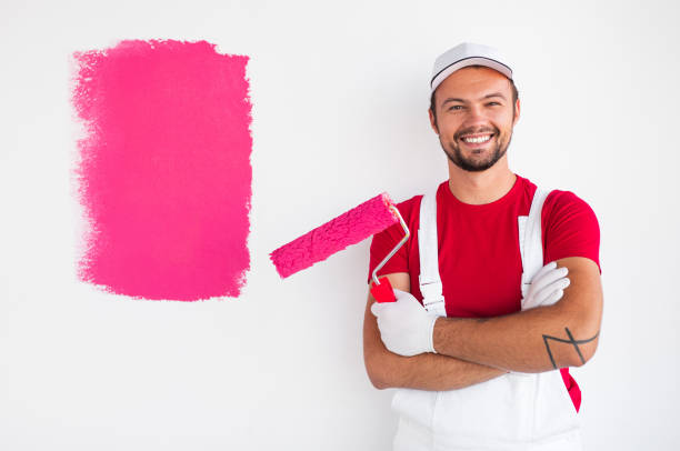 Positive painter standing near sample on wall stock photo