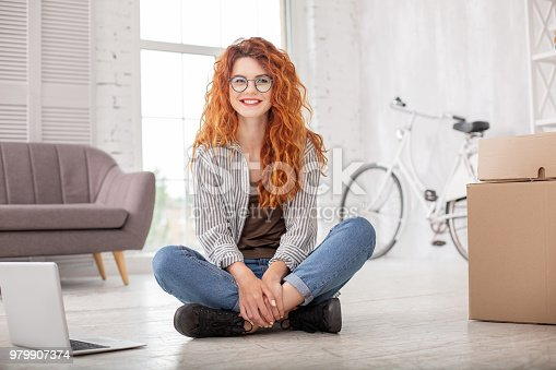 Eager to leave. Cheerful gay woman sitting on floor and smiling to camera