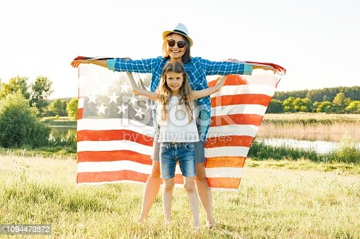 539482224 istock photo Positive portrait of mom and daughter with American flag. Nature background, rural landscape 1094473872