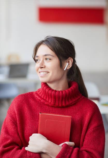 Positive hübsche Mädchen Designer mit drahtlosen Ohrhörer tragen roten strickten Pullover umarmt persönlichen Planer und wegschauen – Foto