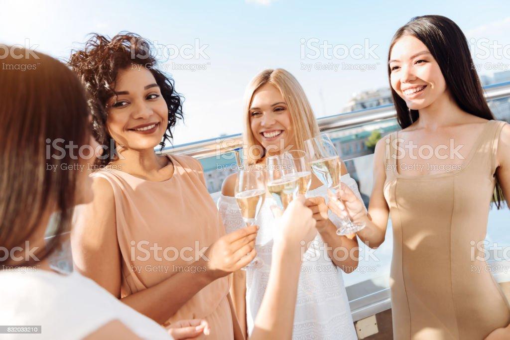 Positive pretty women drinking sparkling wine stock photo