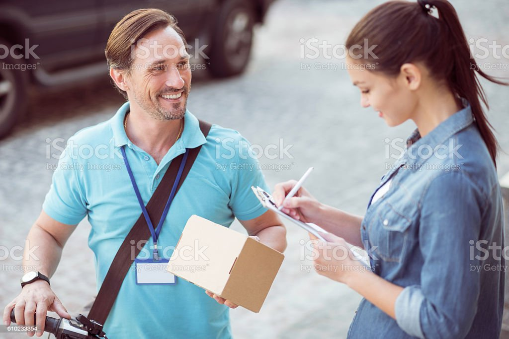 Positive professional courier delivering the parcel stock photo