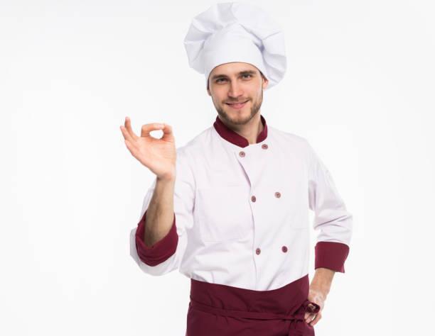 Positive professionelle glücklich Mann Koch zeigt leckere ok Zeichen isoliert auf weißem Hintergrund. – Foto