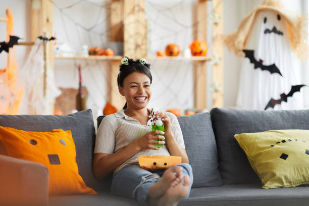 Positive relaxed black woman in headband with toy skulls sitting on sofa and drinking lemonade while watching tv on Halloween stock photo