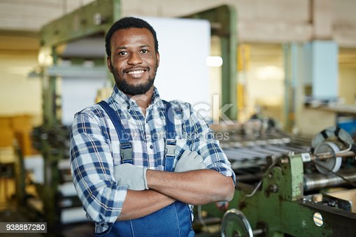 Cheerful handsome bearded African manual worker in gloves crossing arms on chest and looking at camera in printing plant