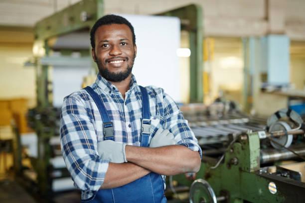 Positive repairman examining printing machine stock photo