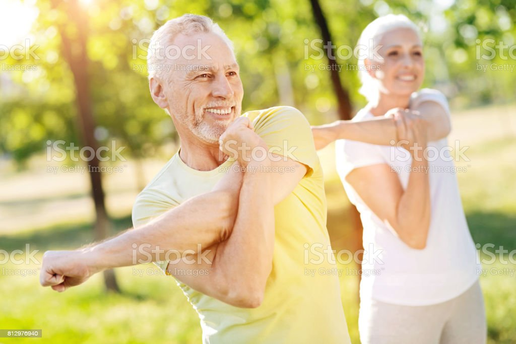 Positive retired couple stretching their hands stock photo